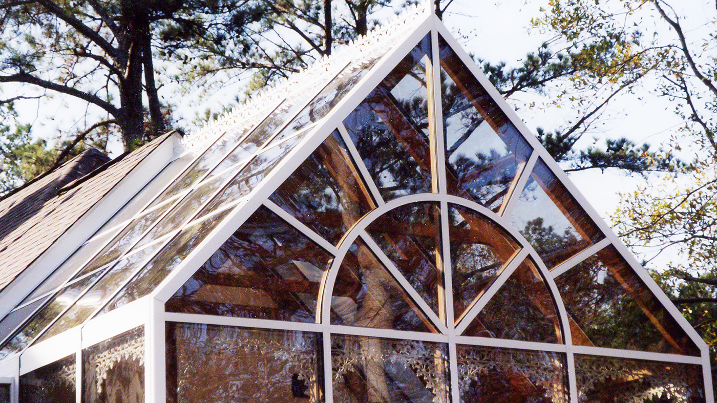 Straight eave double pitch conservatory with a finial, ridge cresting, gable pediment, and decorative corners.