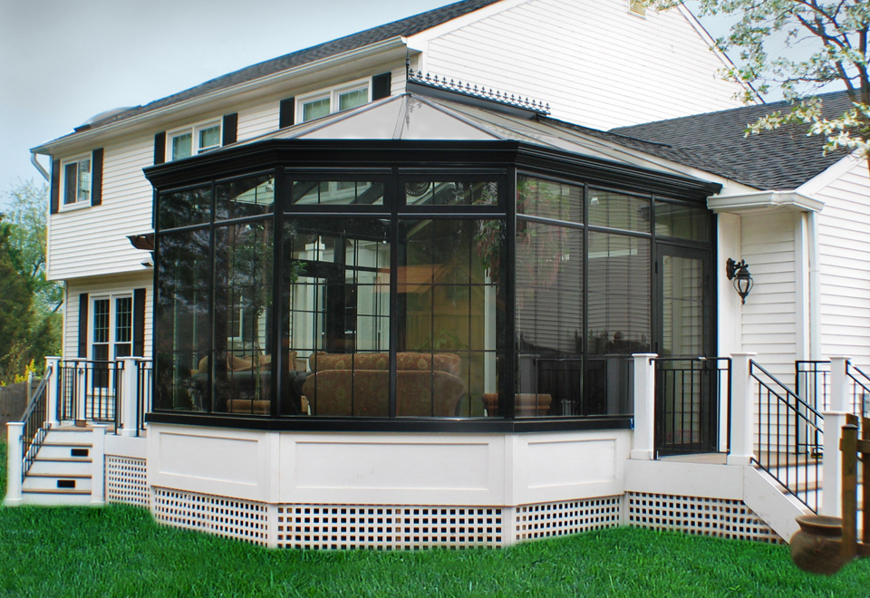 Straight eave, double pitch conservatory with bull nose including transoms, grid work, gutter, finial, and ridge cresting.