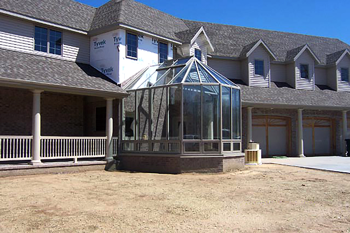 Straight eave double pitch greenhouse with adjoining lean-to framing.