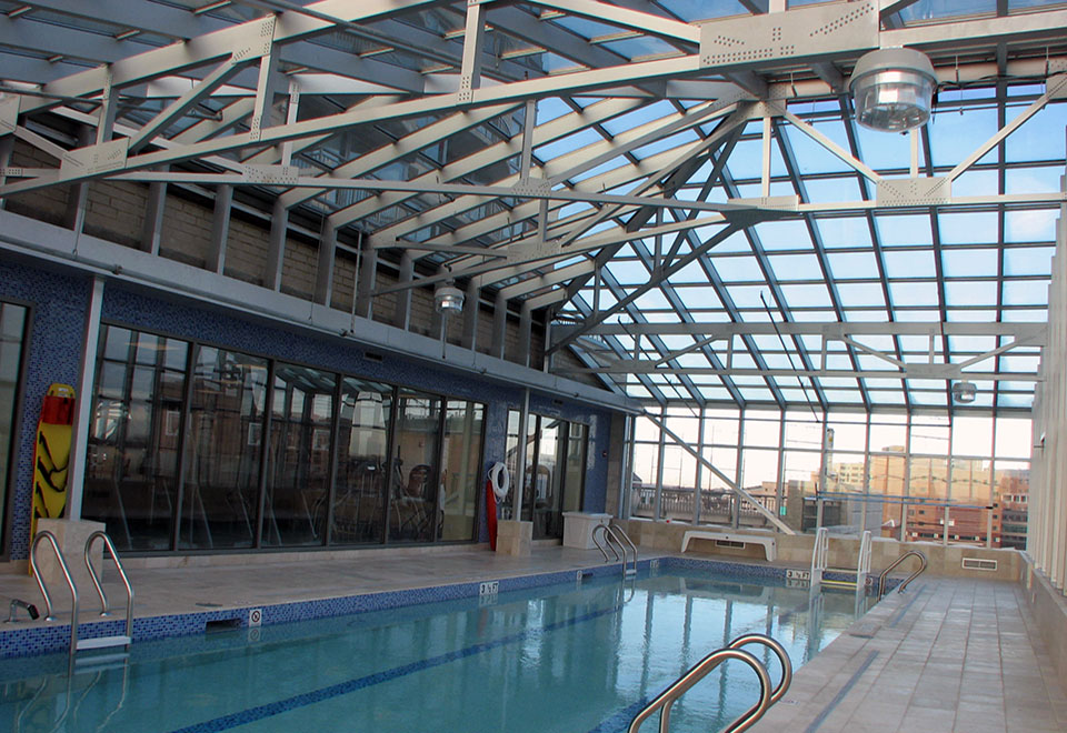 Straight eave double pitch pool enclosure with one gable end and one hip end, ridge vents and awning windows.