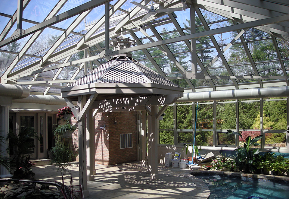 Straight-eave double pitch pool enclosure with two hip ends, one irregular hip corner, two full sidewalls, and one partial end wall. Unit includes awning windows, ridge cresting, finial and terrace door.