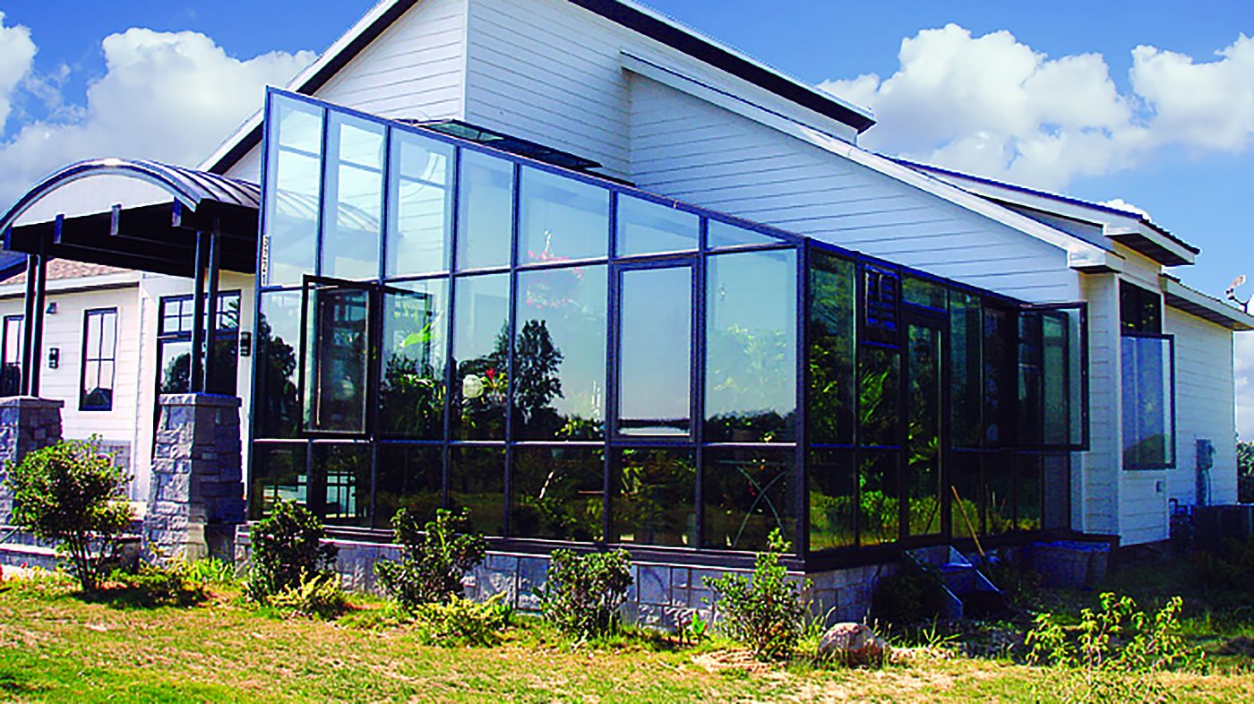 Straight eave lean to greenhouse with one gable end and rear wall with an interior post support. Unit includes ridge vents, shutter fan, motorized intake and casement windows