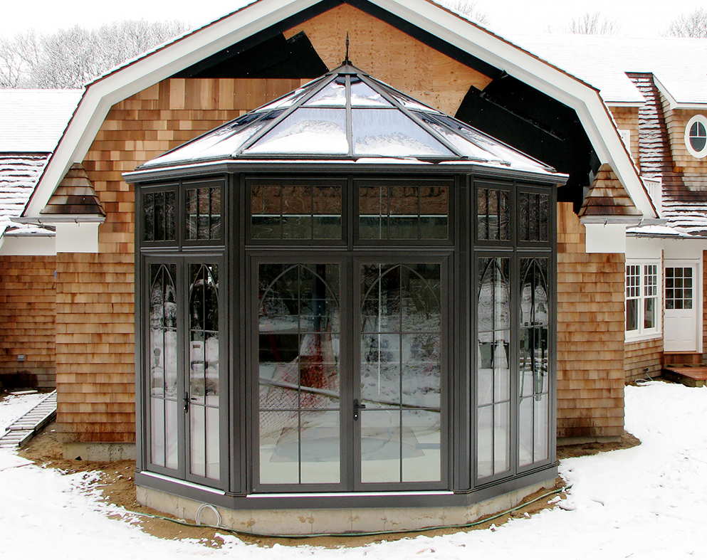 Straight eave double pitch pool enclosure with one conservatory nose, French doors, ridge vents, gridwork, gutter and downspout.