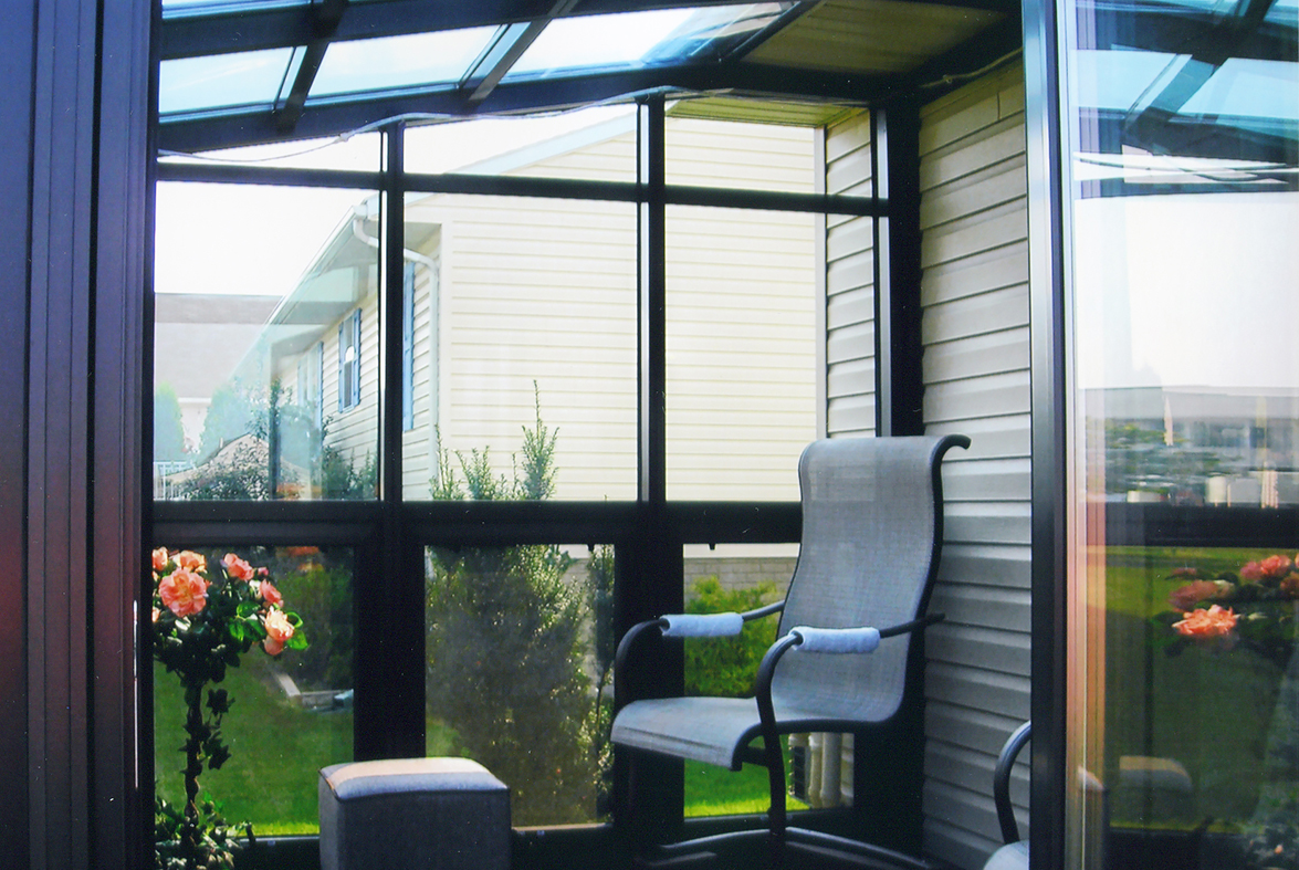 Straight eave lean-to sunroom with terrace door, awning windows, and gutter.