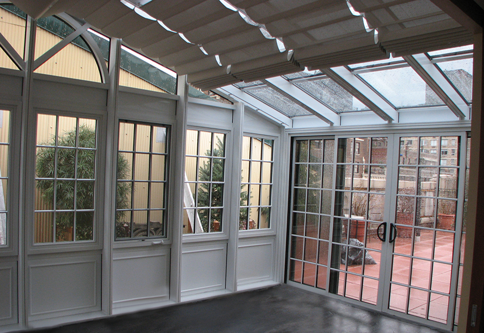 Straight eave double pitch greenhouse with decorative corner post; exterior is standard hartford green duracron and interior is standard white duracron. Unit has operable ridge vents, fixed windows, casement windows, and multi-track sliding/stack.
