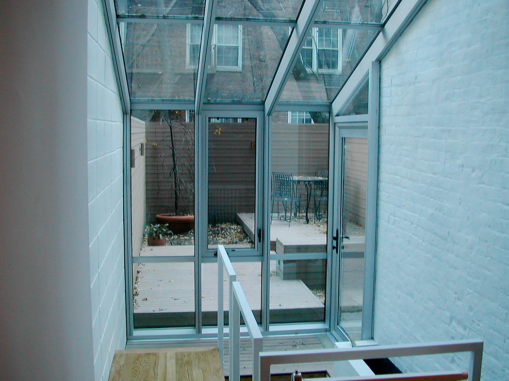 Straight eave lean-to sunroom used to a cover a staircase, including a casement, terrace door and ridge vent