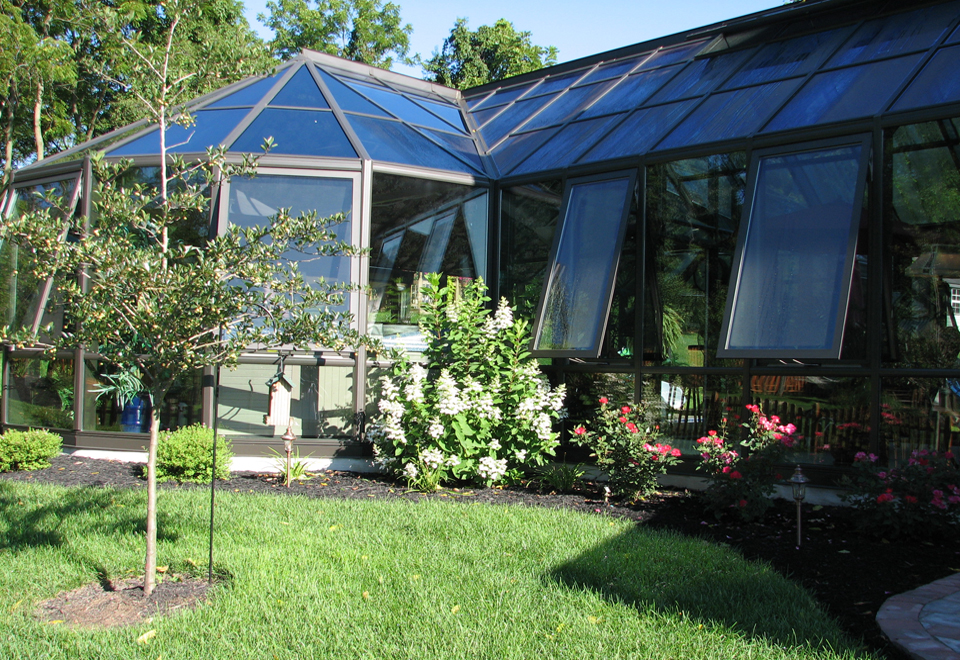 A straight eave double pitch pool enclosure with two conservatory noses and one straight eave double pitch walkway. Uses 4 1/2 and 7 inch aluminum systems, has awning windows, operable ridge vents, and a sliding glass door.