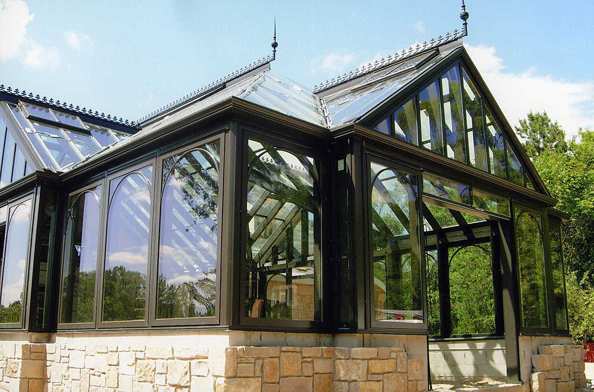 Straight eave double pitch greenhouse with hip end and three attached straight eave double pitch dormers.