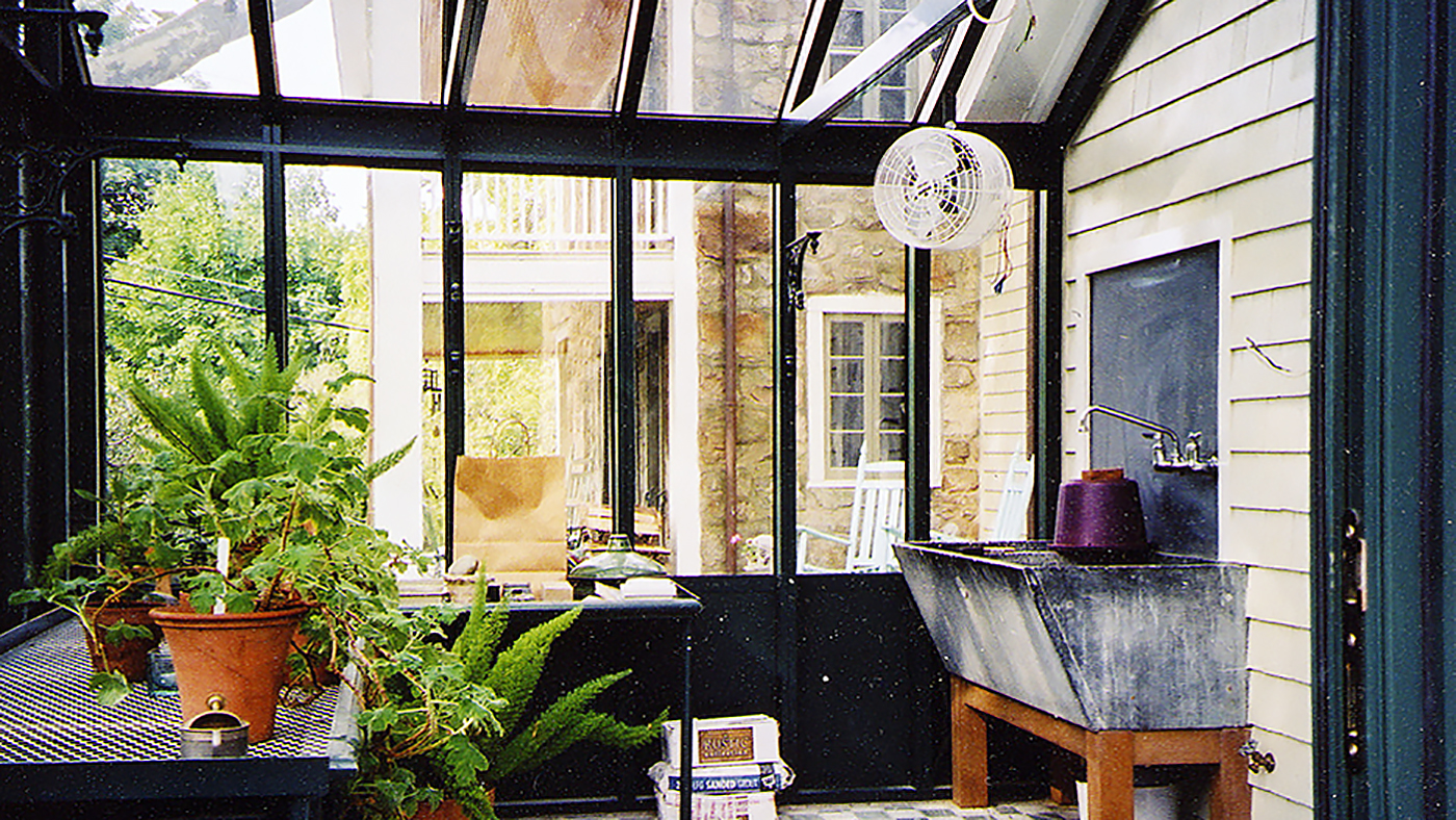 Straight eave double pitch, conservatory greenhouse with decorative base panels, ridge cresting, and operable ridge vents.