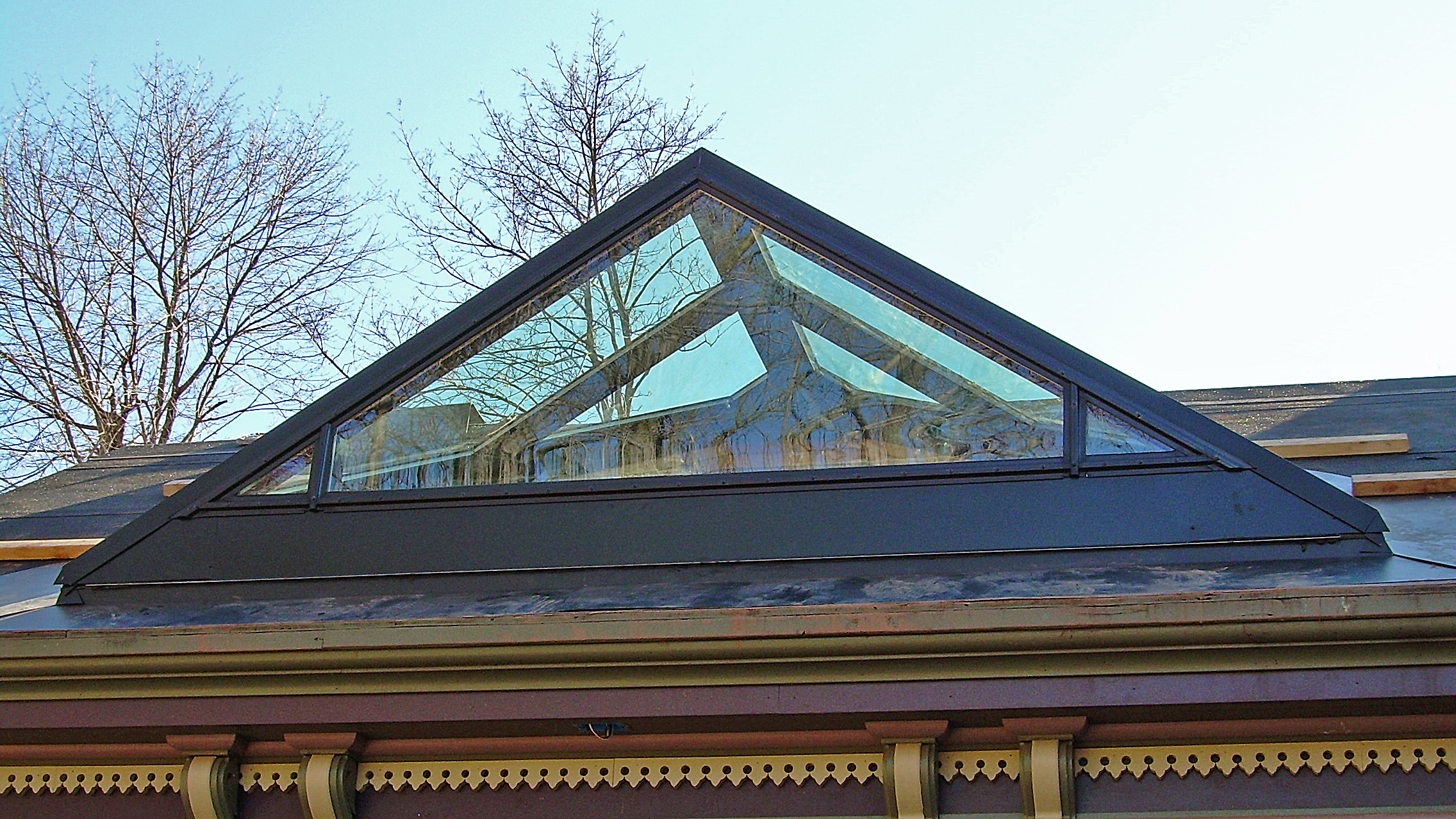 Straight eave double pitch skylights and triangle shaped curtain wall.