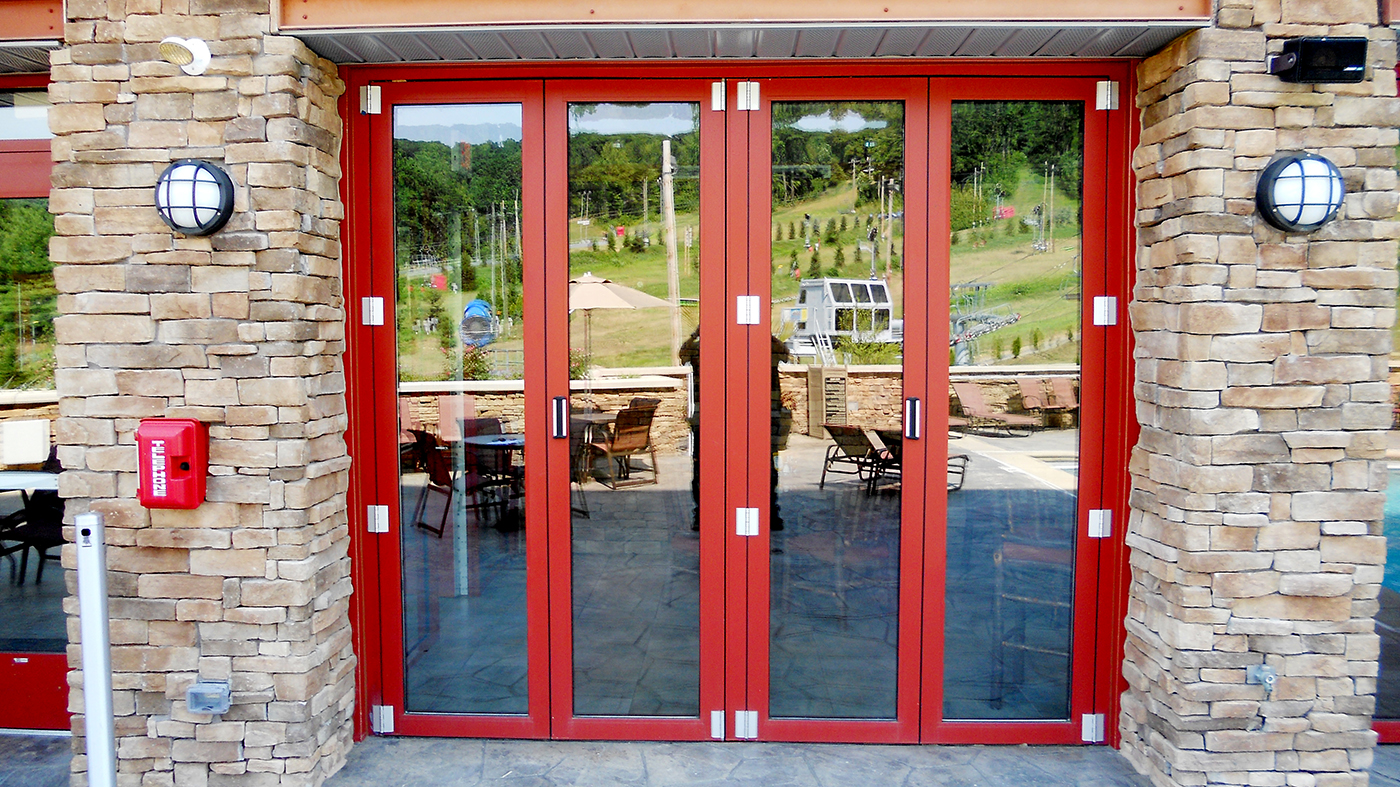 Eight Commercial, Split Wall Folding Glass Walls featuring Custom Red Finish.