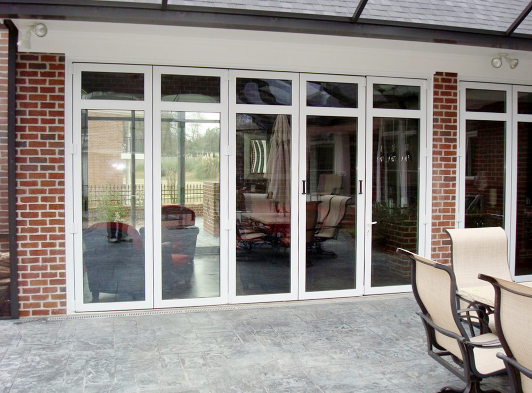 Single jam folding glass wall featuring transom.