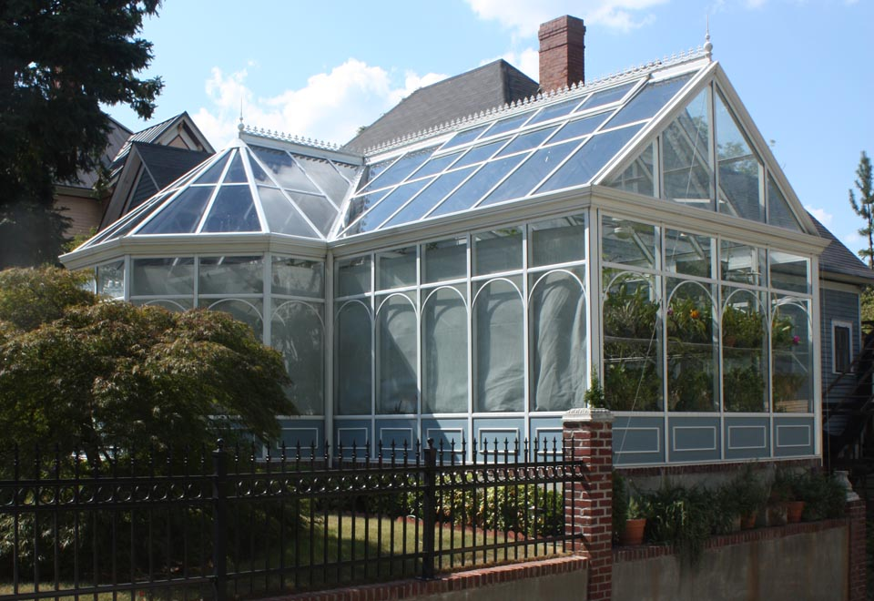 Straight eave, double pitch orchid greenhouse with conservatory nose, partial lean-to roof section, ridge cresting, finials, and grids.