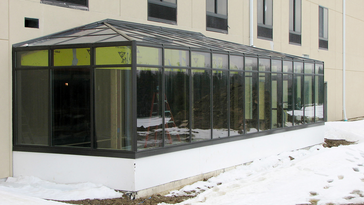 Straight eave lean to pool enclosure with two hip ends and a commercial door.