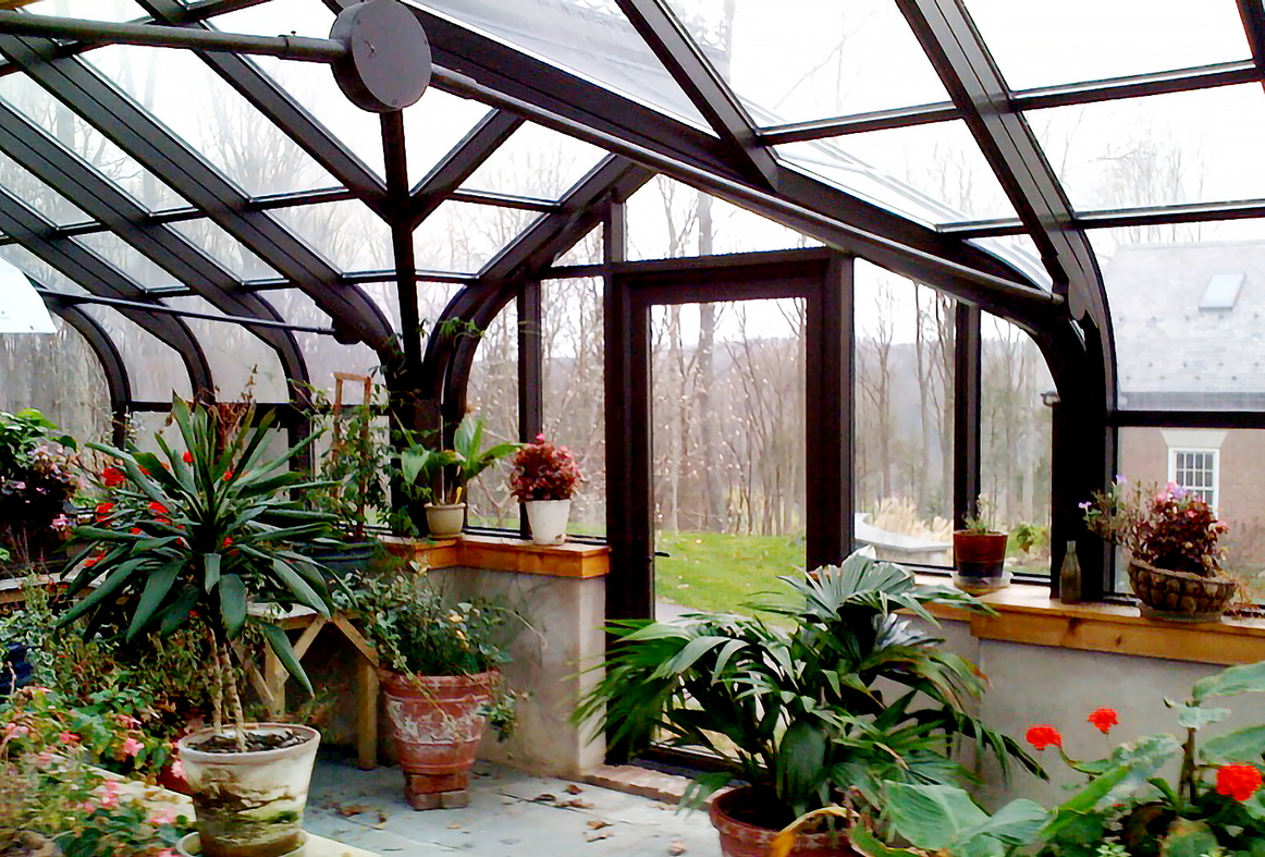Curved eave double pitch greenhouse with two gable ends and a curved eave double pitch dormer with one gable end. Features operable ridge vent, decorative alumnim ridge cresting, terrace door and interior ring and collar.