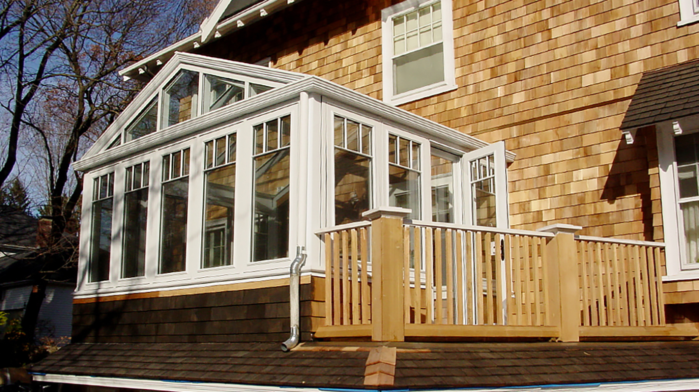 Straight eave double pitch conservatory with one gable end. Structure includes SDL grids designed to mimic a transom, gutter, downspout, crown molding on gable and interior ogee capping.