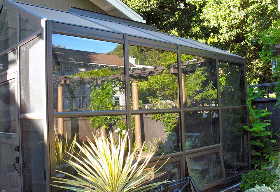Straight eave, double pitch greenhouse with attached lean-to, operable ridge vent, awning windows and decorative raised base panels.