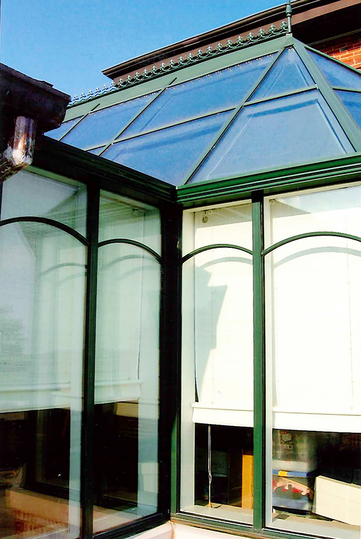 Straight eave lean to sunroom with irregular conservatory nose dormer. Decorative options include: ridge cresting, finial, and SDL grids in a radius arched pattern.