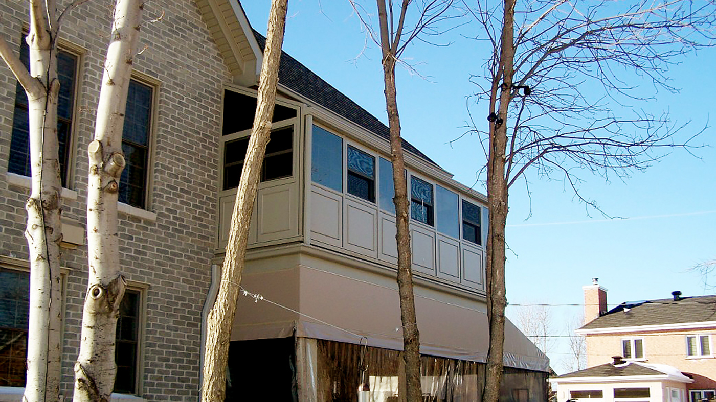 Straight eave lean-to corner sunroom with double-hung windows