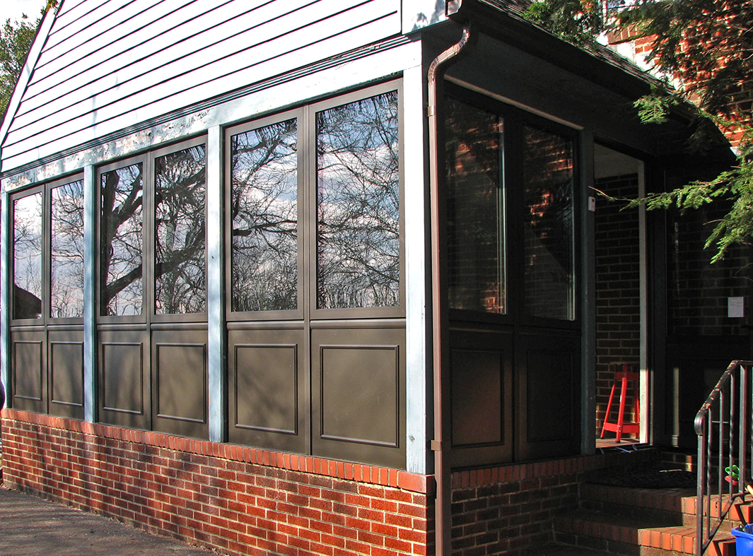 Porch enclosure with outswing door and casement windows.