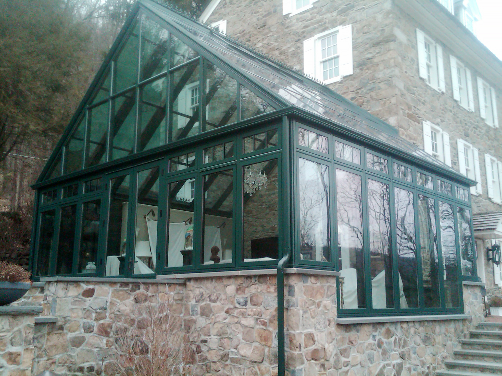 Straight eave double pitch replacement conservatory. Structure was built to replace an older model by another manufacturer. The conservatory has an attached entryway. Decorative accessories include fixed window frames, base panels on the terrace doors, finials, crown molding, transoms, interior ogee and bull nose capping, transoms and SDL's