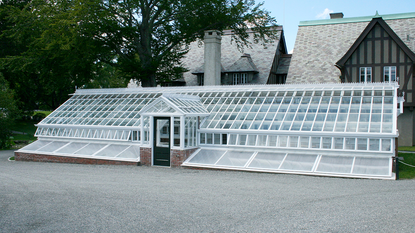 Straight eave, double pitch greenhouse with dormer, ridge cresting, and finial. Restoration System with cold frame.Straight eave, double pitch greenhouse with dormer, ridge cresting, and finial. Restoration System with cold frame.