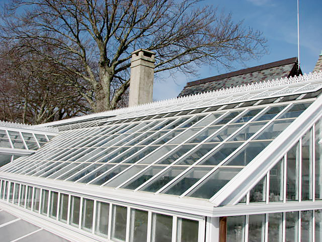 Straight eave, double pitch greenhouse with dormer, ridge cresting, and finial. Restoration System with cold frame.