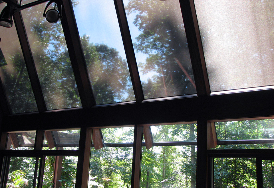 Straight eave lean-to sunroom with no gable ends, retractable exterior screens, mahongany interior, and sliding doors.