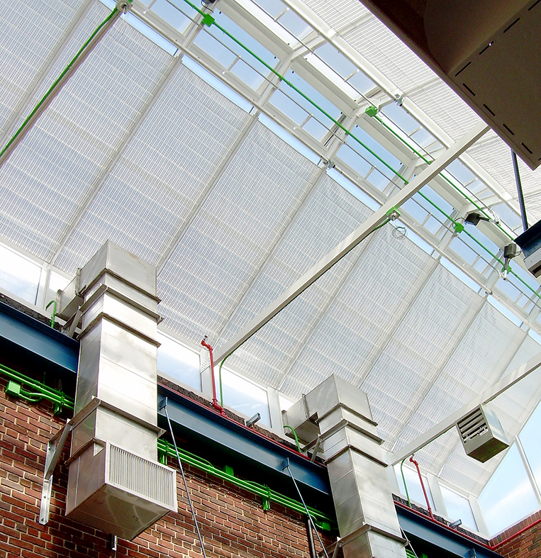 Straight eave double pitch educational greenhouse with only a front wall and sloped roof, constructed out of a vertical curtain wall using polycarbonate and skylight system. Interior accessories include shading, circulation fans, grow lights, misting system, benches, and control system.