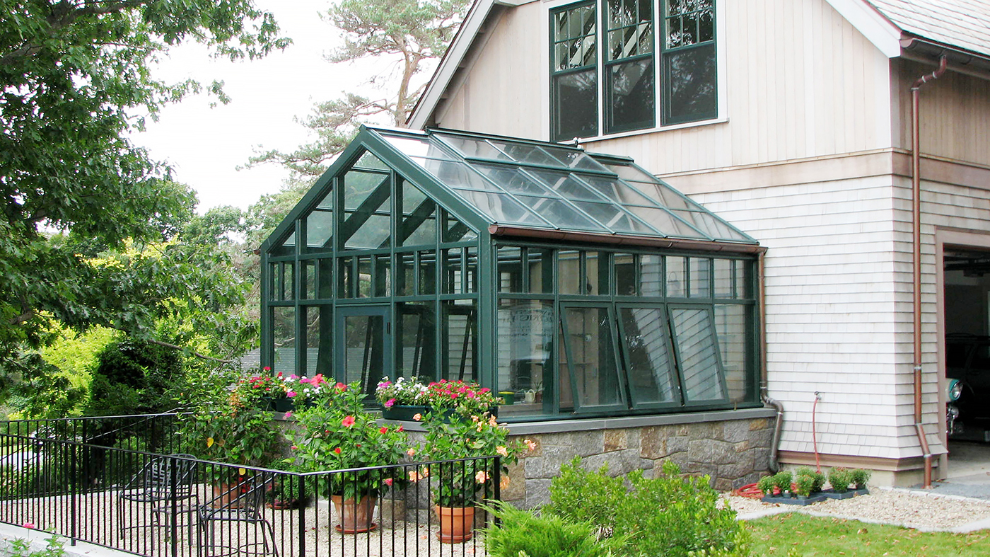 Straight Eave double pitch hobby greenhouse with one gable end, copper gutter, transoms, awning windows, and ridge vents.