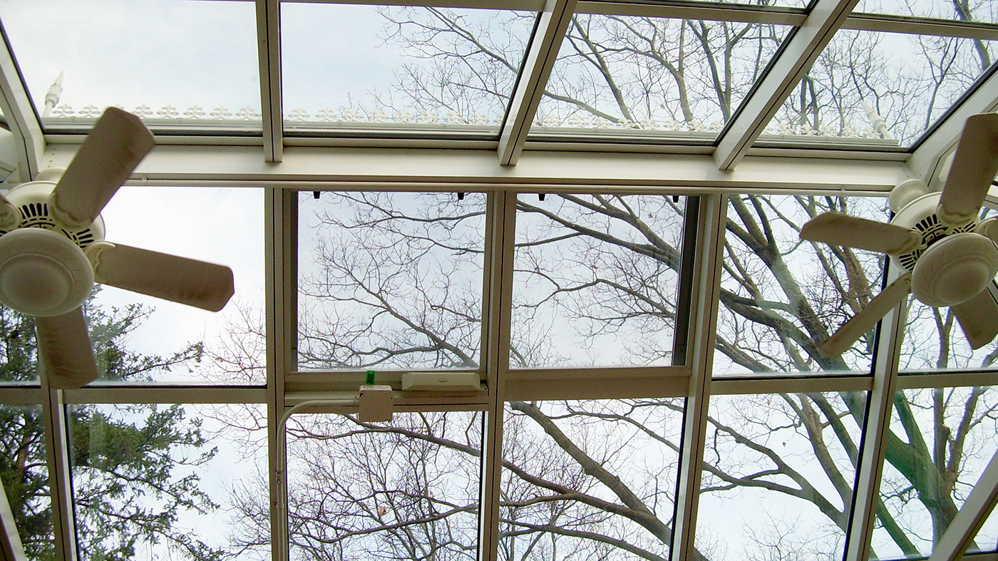 Straight eave, hip end conservatory with transoms, ridge cresting, and finials.