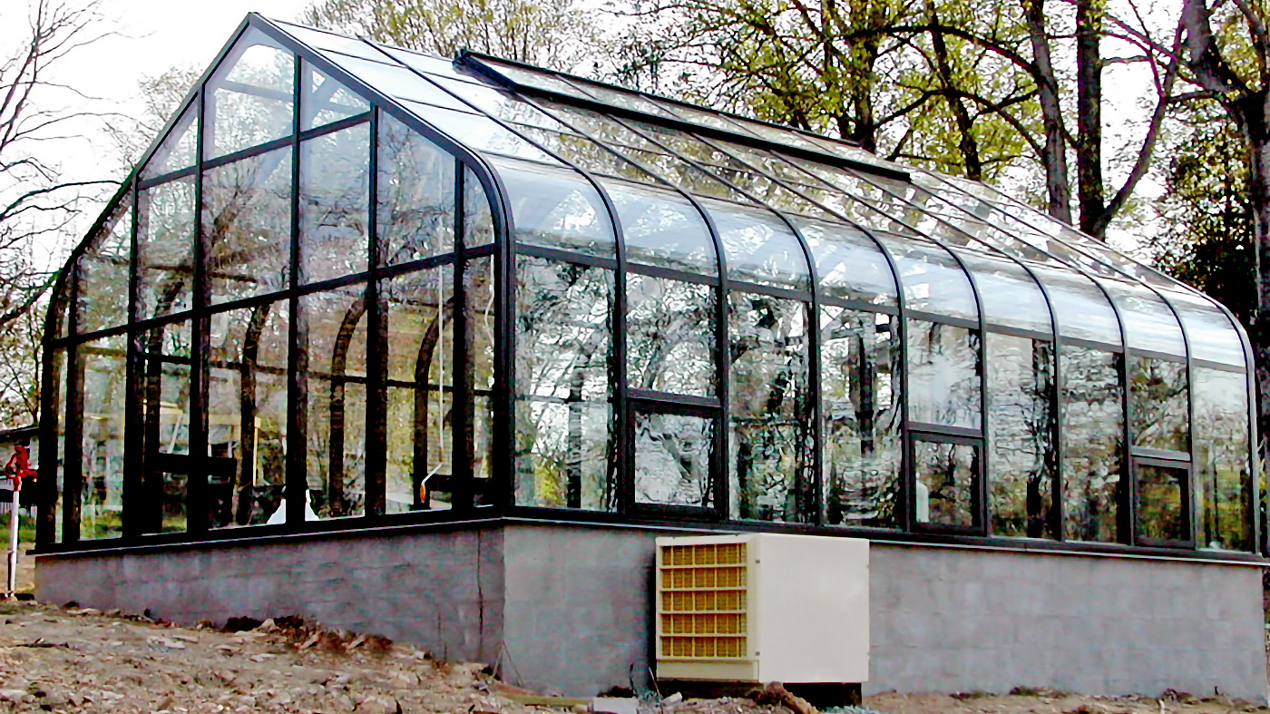 Curved eave, double pitch greenhouse with operable ridge vents, awning windows, terrace door. The interior of the greenhouse features a structural truss system, fixed benches with metal mesh tops, a humdifier and circulation fans.