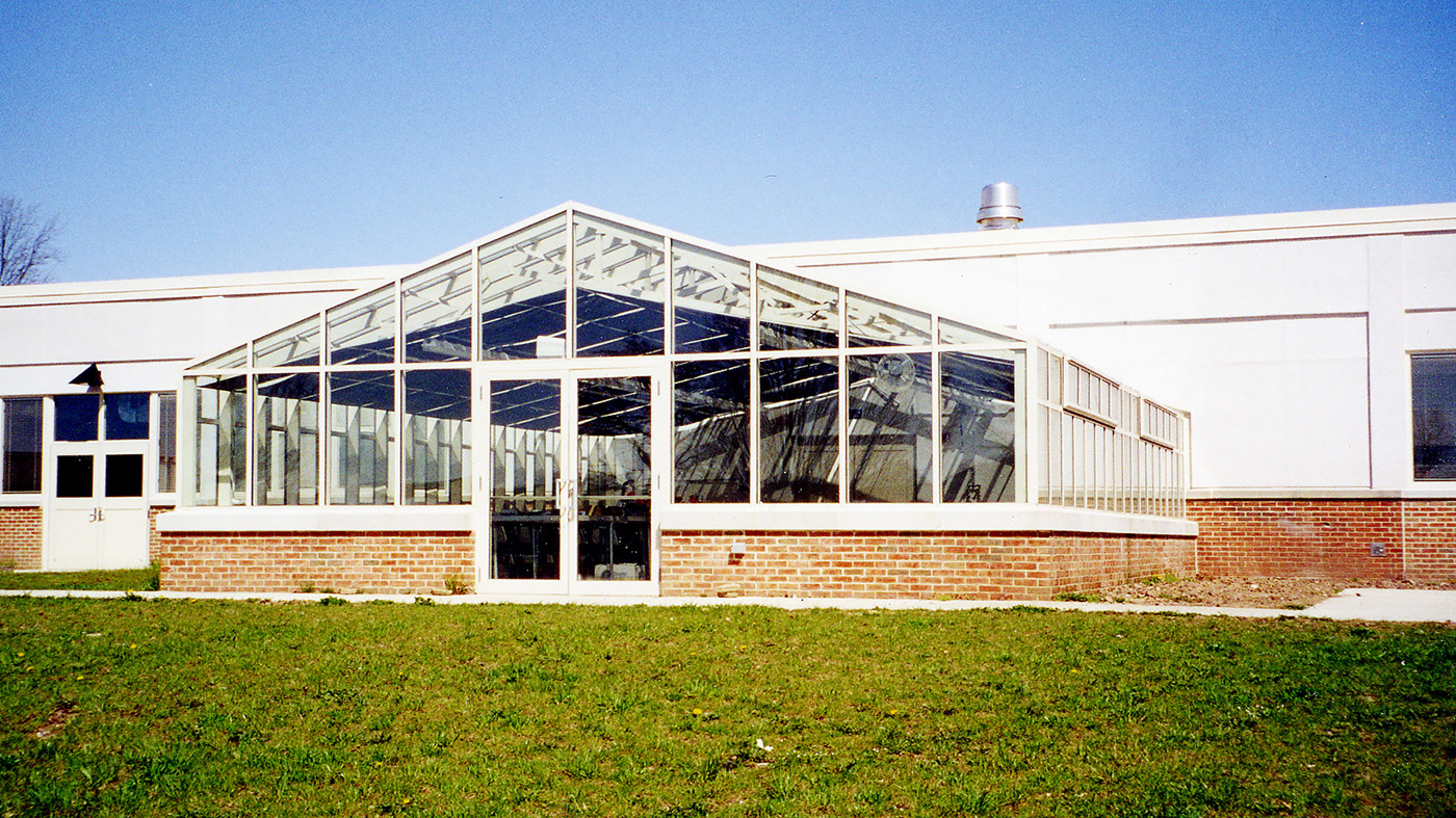 Straight eave double pitch greenhouse with operable ridge and eave vents and interior operable shades.