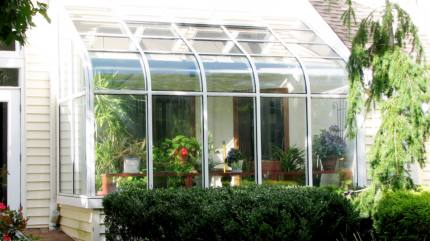 Curved eave, lean-to sunroom with operable ridge vent.