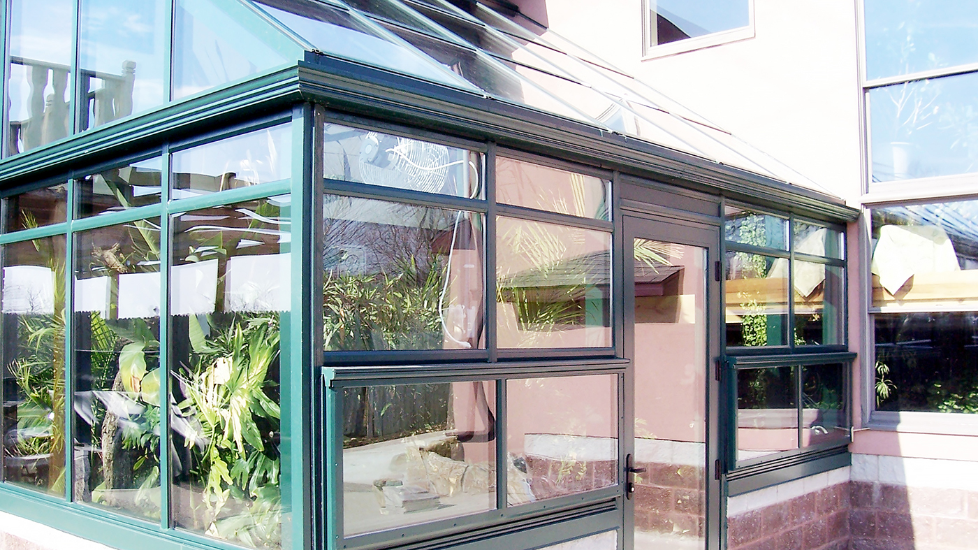 Straight eave lean to greenhouse with one gable end used to grow palm trees and tropical plants, including ridge vent, eave vent, terrace door, gutter and downspout.
