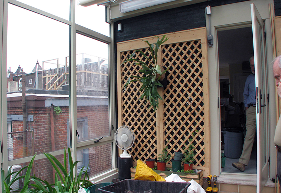 Straight eave lean-to greenhouse with one gable end, located on a rooftop. Greenhouse includes terrace door, ridge vents and interior roof mounted operable shades.