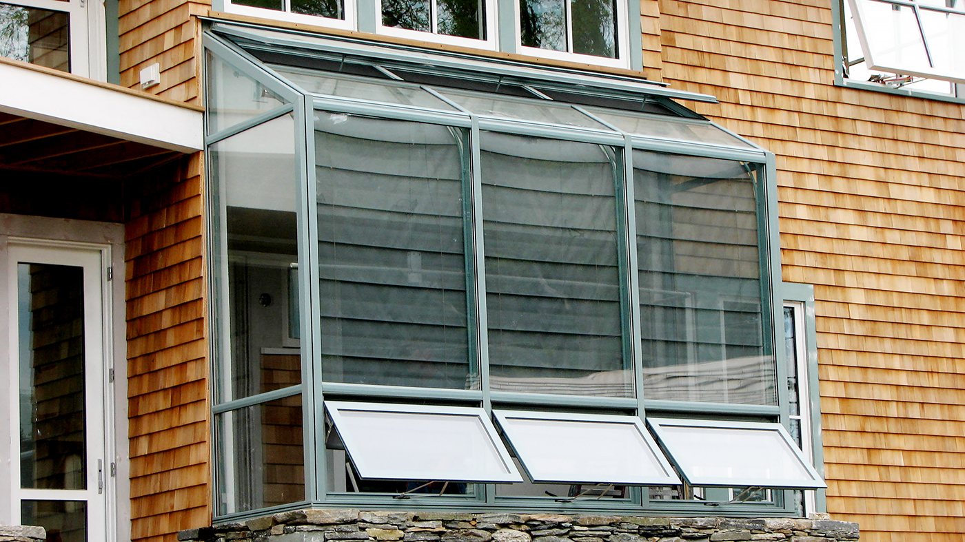 Straight eave lean-to hobby greenhouse with two gable ends, ridge vents, awning windows, interior Roman fold shades, humidifier and environmental control system.
