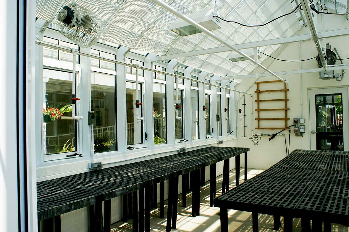 Straight eave double pitch greenhouse used at a retirement community. Unit includes ridge vents, transoms with grids, casement windows, terrace door, interior circulation fans, grow lights and interior roof mounted shades.
