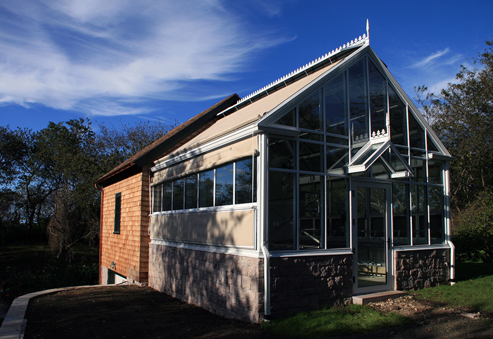 Straight eave double pitch greenhouse with one gable end and a straight eave double pitch canopy. Unit also includes ridge vents, eave sash, gable rake, gutter, downspout, finial, ridge cresting and exterior roll up shades.