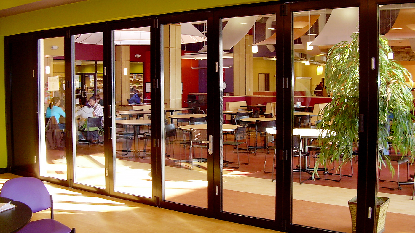 Folding glass wall system with ten panels, a double door midwall. Featured in a black frame finish.