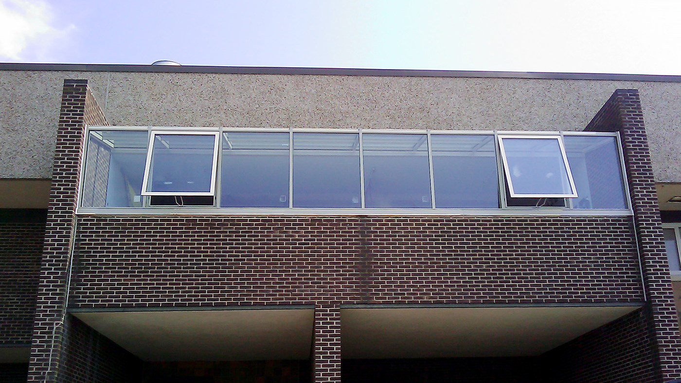 Straight eave lean-to sunroom in sandstone built at a school in New Jersey.