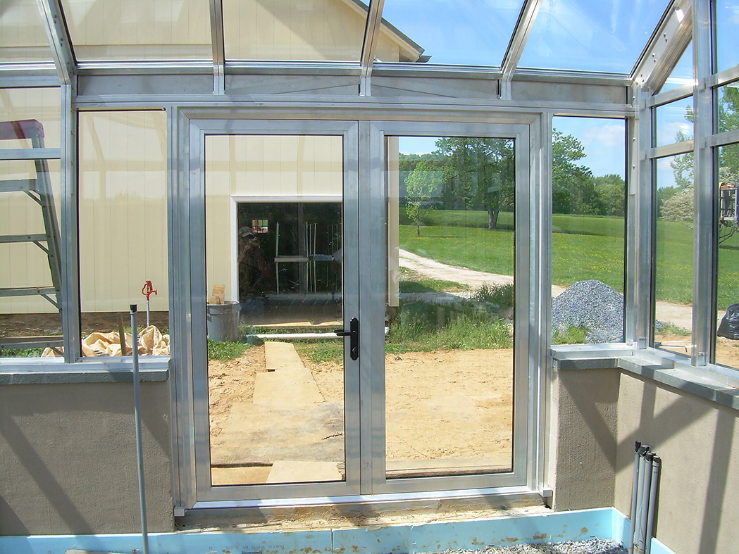Straight eave double pitch I-Beam greenhouse with two gable ends; includes French door, operable ridge vents, evaporation coolers, shutter fan, and greenhouse benches.