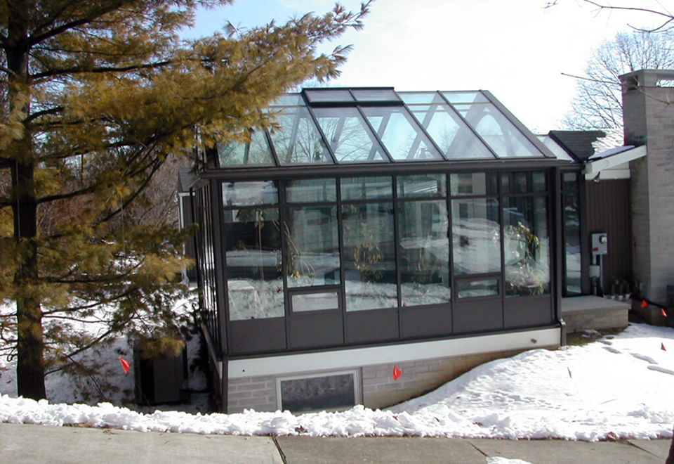 Custom Sunroom configuration: (1) straight eave double pitch and (1) straight eave lean-to Sunroom connected by an enclosed walkway. Decorative elements include: radius arch in gable end, solid base panel, gutter, and downspouts.