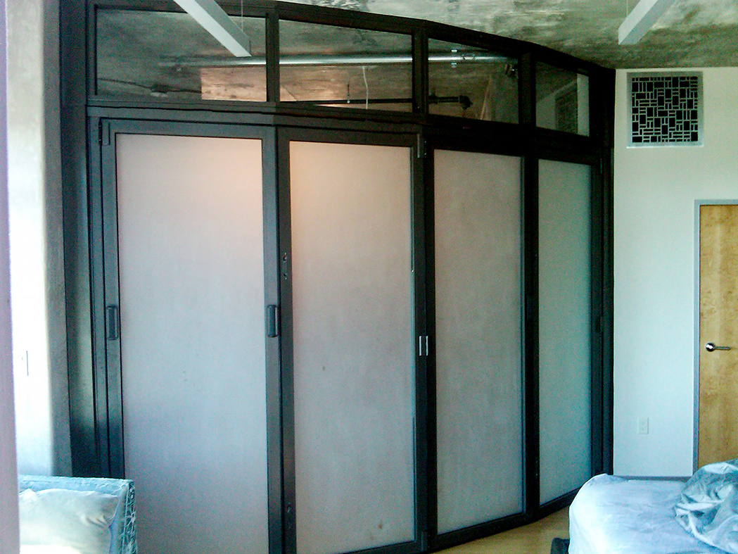 Two interior folding wall systems used on a residential application. One unit is an all wall segmented radius configuration with a segmented transom above and utilized a recessed sill. The second unit is a straight all wall configuration with a transom above and a flush mount sill.