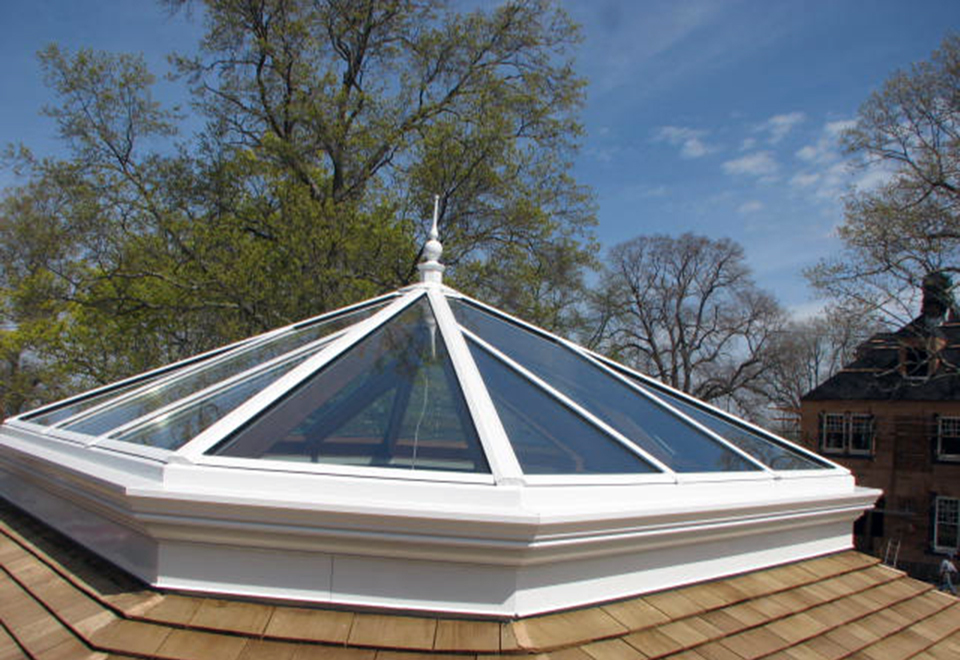 Irregular pyramid skylight with four hip ends. Interior ogee on face of all rafters, bullnose sill extension, and exterior finial.