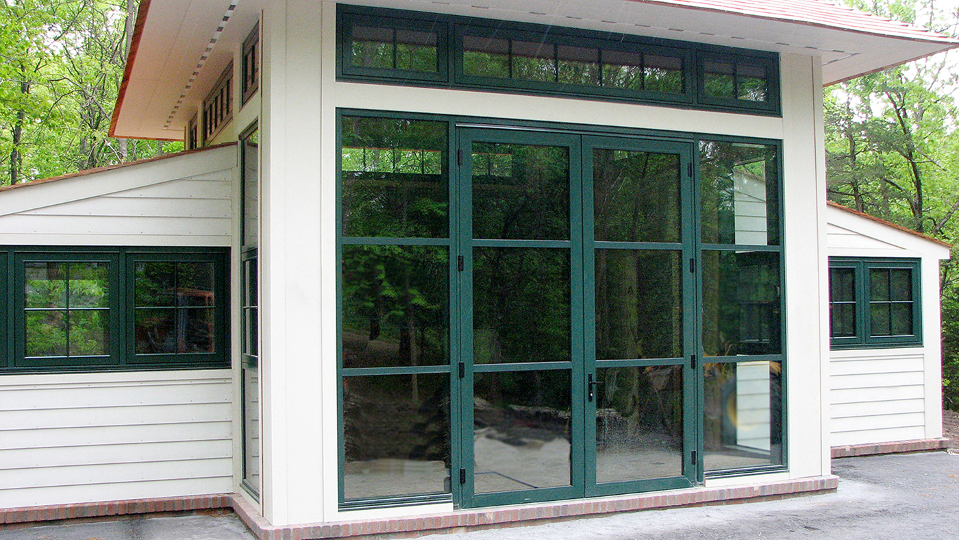 Vertical curtain wall systems with SDL grids and awning windows.