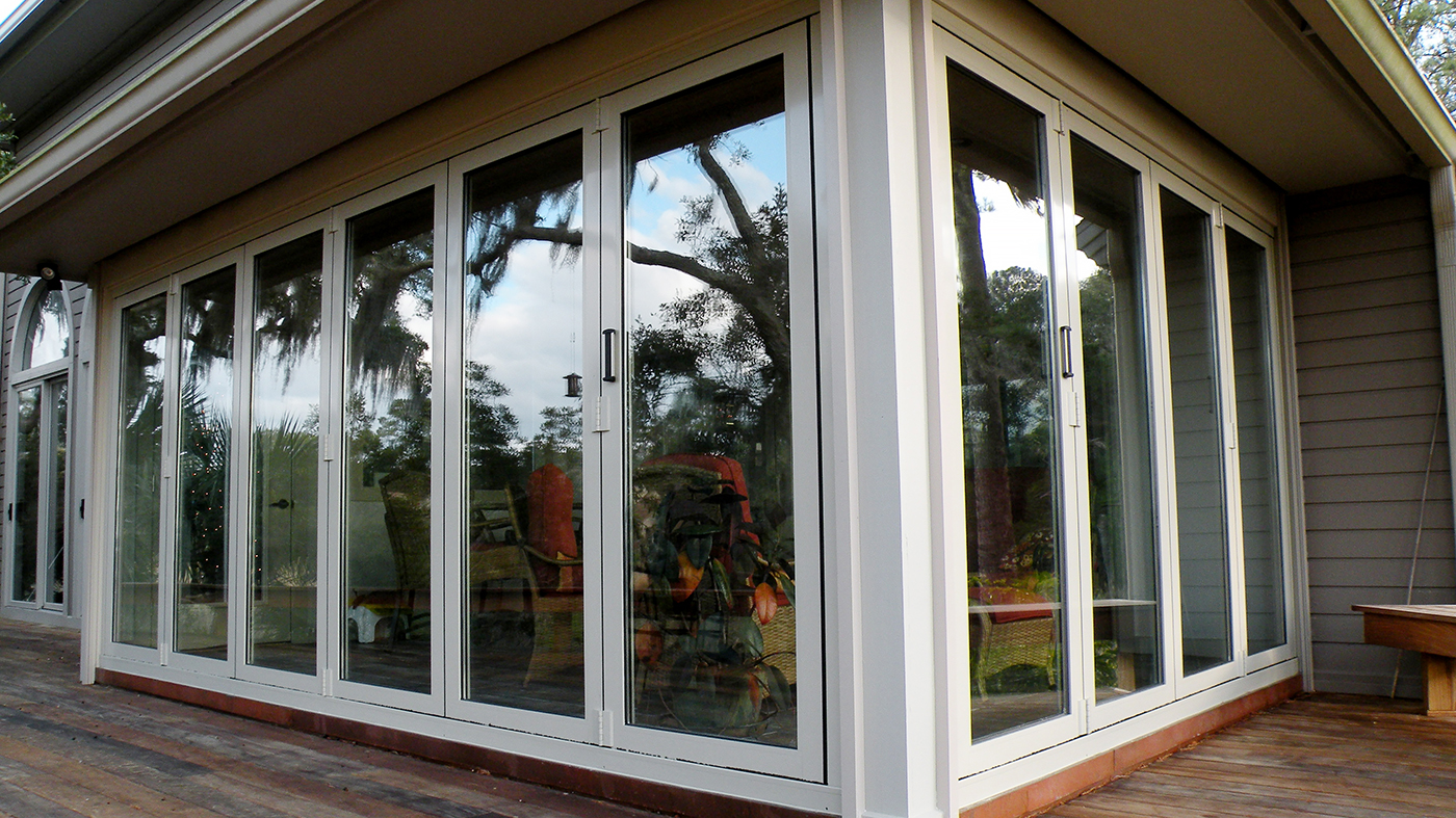 Two folding glass wall units, one with six panels folding left, the other with four panels folding right, standard sill.
