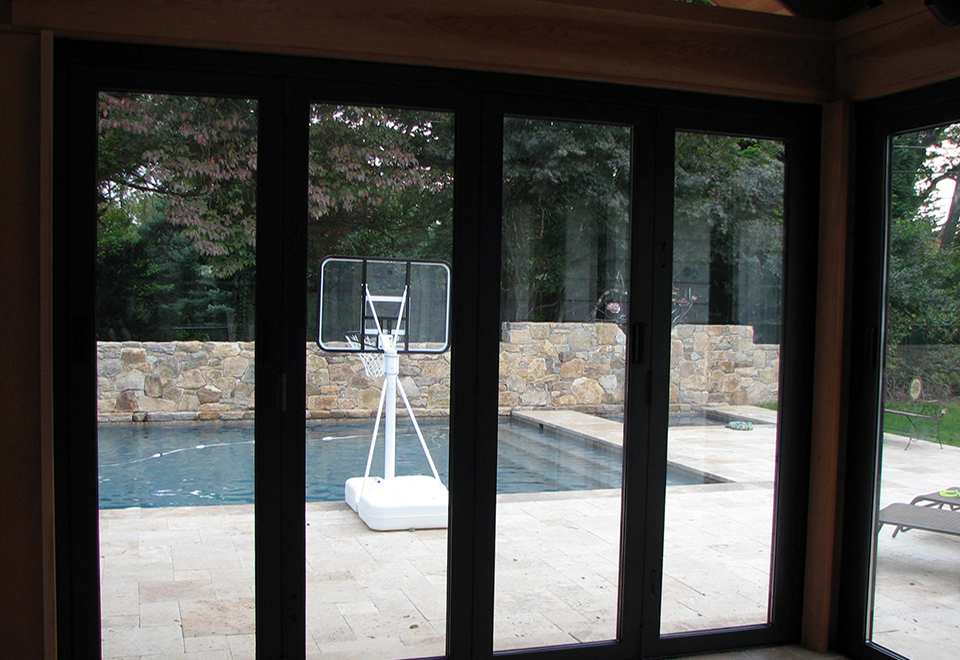 Three all wall configuration folding glass wall units with recessed sills used on a pool house. Out-swing residential terrace door with butt hinges, mortise lock with deadbolt and doggie door.
