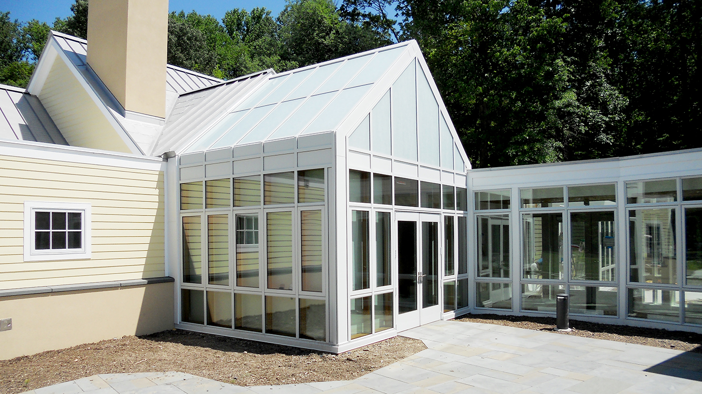 Straight eave double pitch sunroom with one gable ends. Structure has an aluminum exterior framing system and a Douglas Fir interior. The sunroom features specialty Solera glass, motorized and fixed shades, operable windows, and a commercial terrace door.