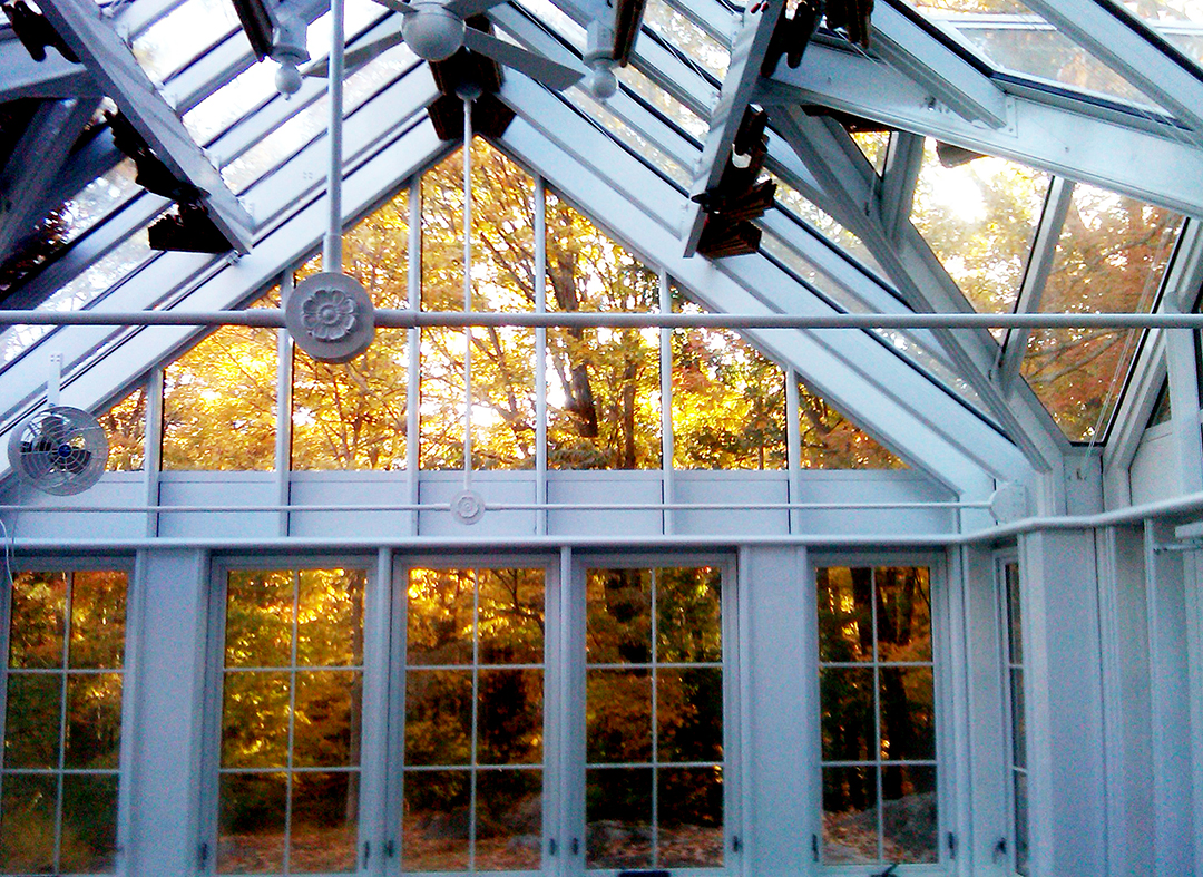 Straight eave double pitch greenhouse with one gable end two attached double pitch dormers and one pyramid cupola.